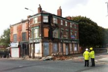 Part of an abandoned pub building collapsed in Kensington, narrowly missing a pensioner and causing travel chaos.