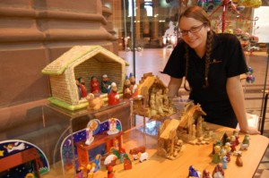 Liverpool Cathedral shop assitant with some of the Nativity sets ©Facebook-Liverpool Cathedral