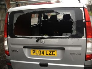 The smashed back window of the van where the equipment was left.