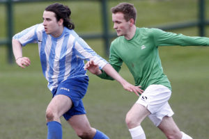 Alumni two-goal star Adam Jones (right) takes on Level 2's Cieran Simpson. Pic © Craig Galloway