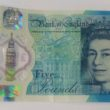 A woman hopes to get more than £1,500 after selling a rare £5 note with a misprint on the new plastic currency.