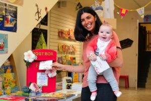 A new mother posting her letter in the red post box. Pic © Jessica Farmery