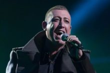 Liverpool's Chris Maloney is through to the next stage of X Factor amid a war of words between judges Gary Barlow and Tulisa.